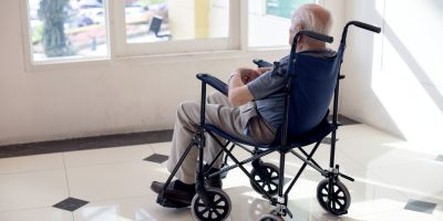 old man sit on wheelchair looking out to from the room