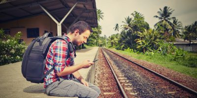 Young traveler with mobile phone on the railway