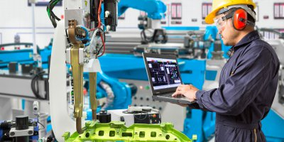 Engineer using laptop computer maintenance automatic robotic hand machine tool in automotive industry manufacturing factory