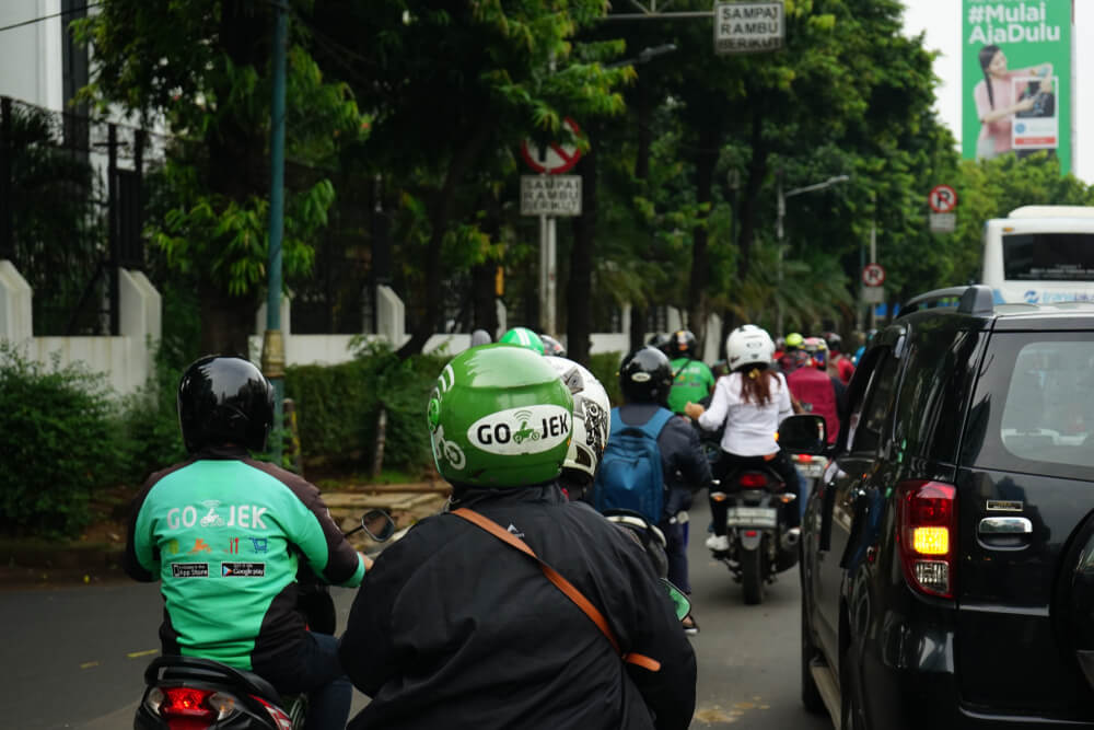 a gojek rider taking passengers in indonesia