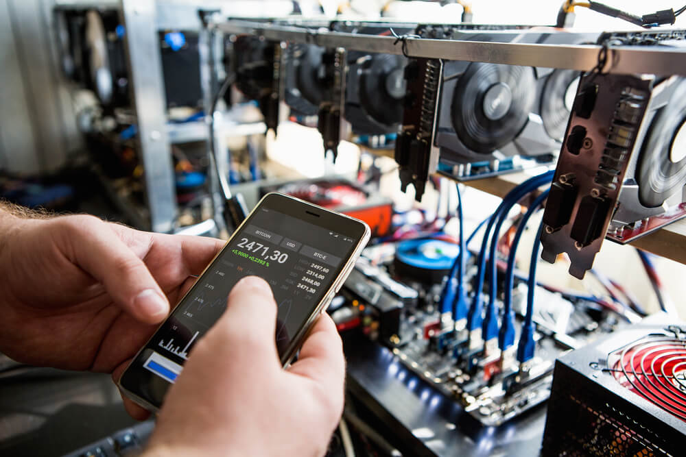 a person checking the bitcoin exchnage in front of a mining rig